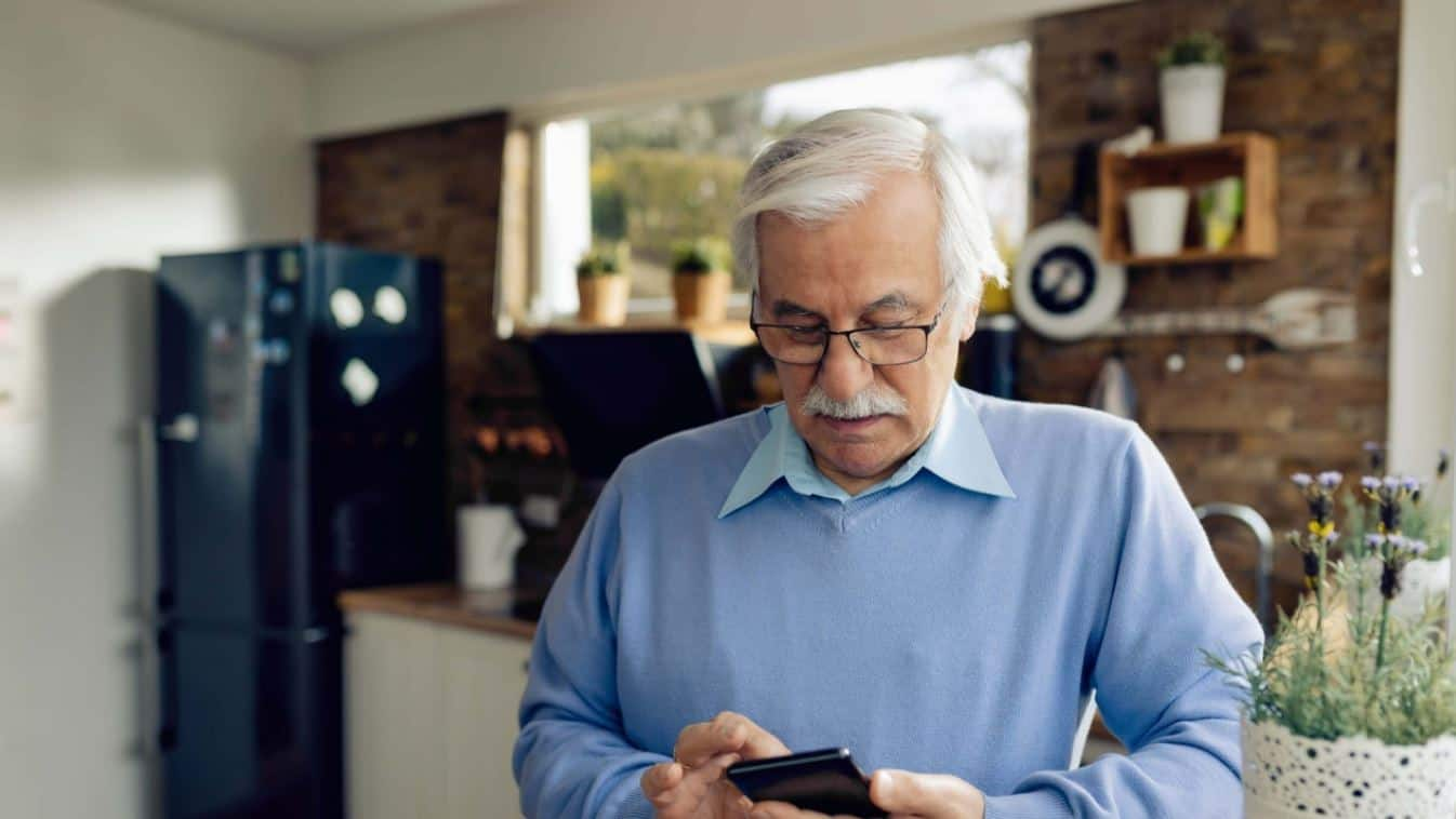aging man on mobile phone