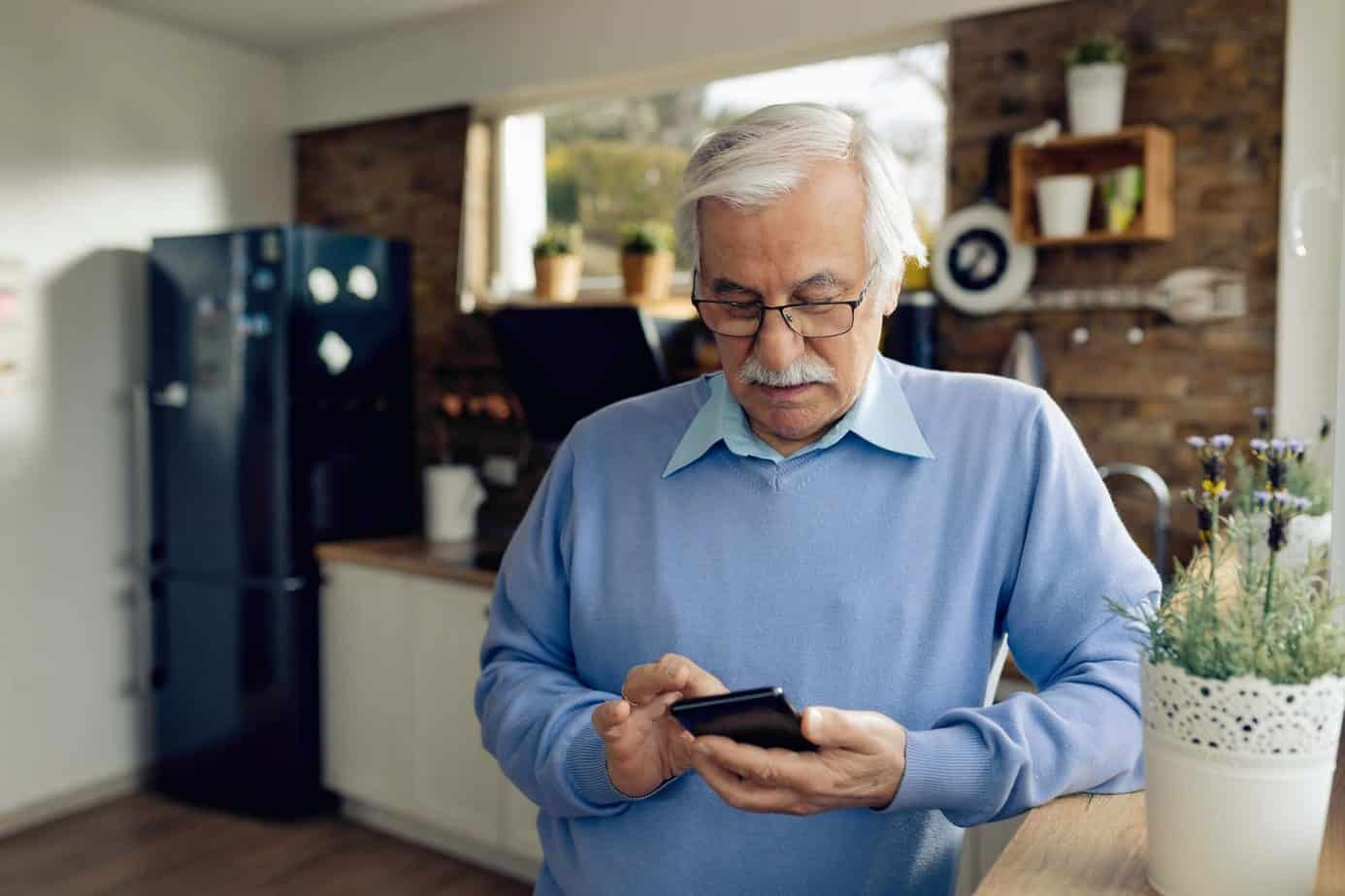 Senior man text messaging on mobile phone in the kitchen