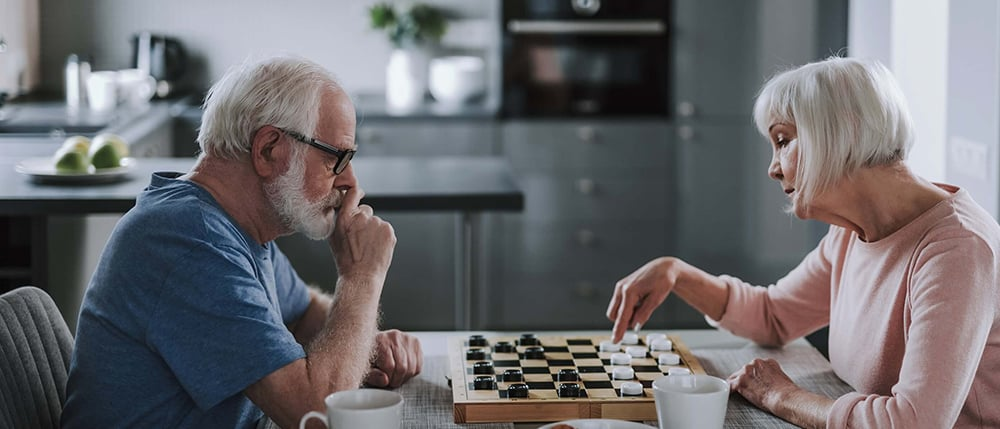 Elder-pensioner-couple-playing-checks-at-home-1000x429