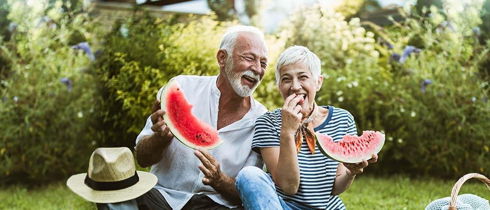 senior-couple-having-fun-while-eating-watermelon-in-the-backyard-1000x429